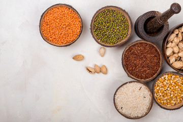 cereals, seeds, beans, grains in a bowls on white table, top view
