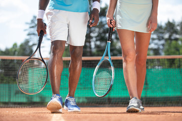 Close up of male and female legs while playing tennis in open air. Couple is walking along playground during break. They are holding rackets