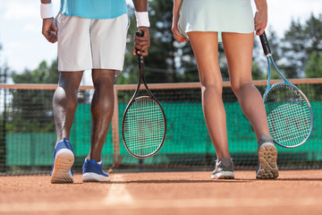 Close up of male and female sports people legs while playing active game. They are standing on court with focus on back and holding rackets. Team mates are preparing for match