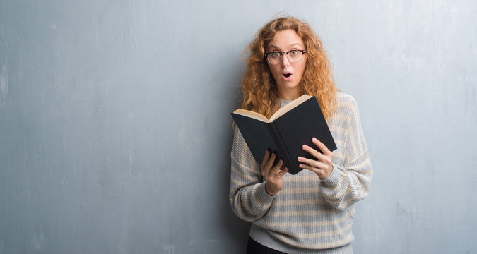 Young redhead woman over grey grunge wall reading a book scared in shock with a surprise face, afraid and excited with fear expression