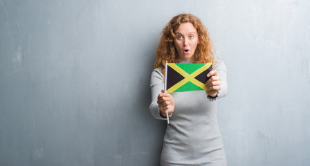 Young redhead woman over grey grunge wall holding flag of Jamaica scared in shock with a surprise face, afraid and excited with fear expression