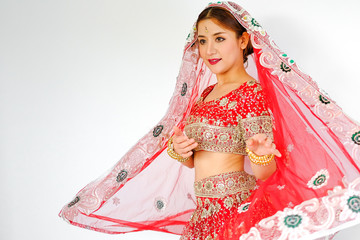 Beautiful indian girl. Young hindu woman model and kundan jewelry Traditional Indian costume red saree. Indian or Muslim woman covers her face