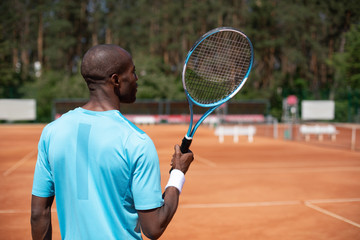 Sportsman is having tennis match on sunny court. He is standing and holding outfit in right hand while getting ready for receiving ball. Active leisure concept