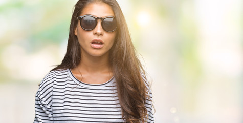 Young beautiful arab woman wearing sunglasses over isolated background afraid and shocked with surprise expression, fear and excited face.