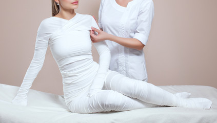 The cosmetologist wraps the leg of the customer. Anti-cellulite procedure-STYX wrap.