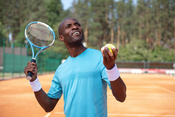 Sportsman is going to strike ball on court. He is holding racket and while looking up. Man is throwing up outfit while being server in match