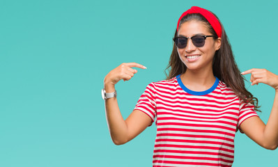 Young beautiful arab woman wearing sunglasses over isolated background looking confident with smile on face, pointing oneself with fingers proud and happy.