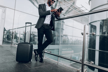 Smart and urban. Low angle portrait of businessman is using pc tablet while waiting for his taxi. Suitcase is standing near him