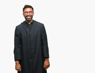 Adult hispanic catholic priest man over isolated background sticking tongue out happy with funny expression. Emotion concept.