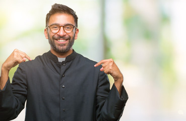 Adult hispanic catholic priest man over isolated background looking confident with smile on face, pointing oneself with fingers proud and happy.