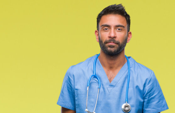 Adult hispanic doctor or surgeon man over isolated background with serious expression on face. Simple and natural looking at the camera.