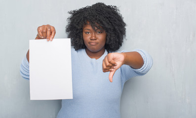 Young african american woman over grey grunge wall holding blank paper sheet with angry face, negative sign showing dislike with thumbs down, rejection concept