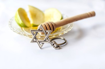 Rosh Hashanah Jewish New Year concept image. Apples with honey and wooden honey stick on a plate and a Star of David key chain on a white table background.