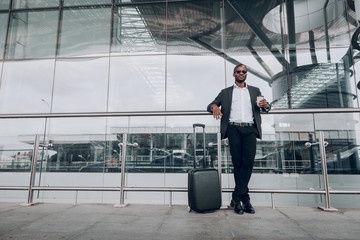 Nice duty journey. Full length portrait of man waiting for taxi enjoying coffee outside the airport. He feeling satisfied about his business trip. Copy space in left side
