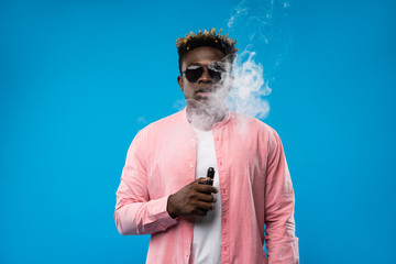 Feeling relaxed. Waist up portrait of afro guy holding vape device and surrounded by cloud of smoke. He is wearing pink shirt and sunglasses. Isolated on blue background