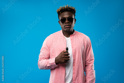 10b71f77 Waist up portrait of young man standing with vape device in hand. He is  wearing pink shirt and sunglasses. Isolated on blue background