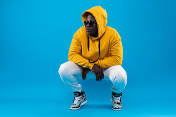 My style. Studio portrait of young man in yellow hoodie hunkering down and looking away with calm expression