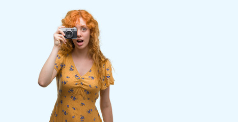 Young redhead woman taking pictures holding vintage camera scared in shock with a surprise face, afraid and excited with fear expression