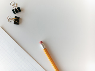 White Desktop with paper clips, graph paper and a pencil with copy space.