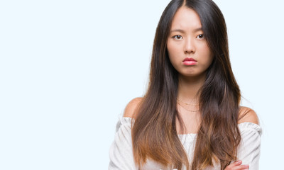 Young asian woman over isolated background skeptic and nervous, disapproving expression on face with crossed arms. Negative person.