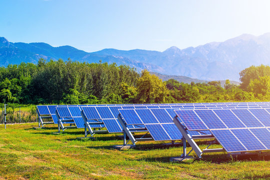solar panels in field surrounded by mountains