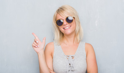 Adult caucasian woman over grunge grey wall wearing retro sunglasses very happy pointing with hand and finger to the side