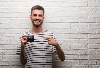 Young man holding vintage camera standing over white brick wall very happy pointing with hand and finger