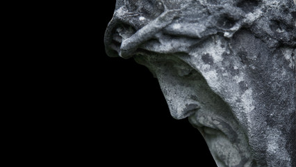 Fototapete - An ancient statue of the crucifixion of Jesus Christ in profile against black background