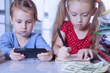Business child girls with dollar banknotes and mobile phone keeping track of the stock market. (Perspective, profit, risk, loss, wealth concept)