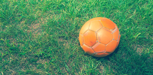 Orange soccer ball on green grass. The concept of street football. An old ball with cracks. Healthy lifestyle. Sport. Victory.