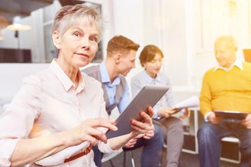 Alte Frau mit Tablet Computer bei Business Meeting