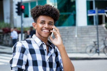 Laughing african american young adult at mobile phone