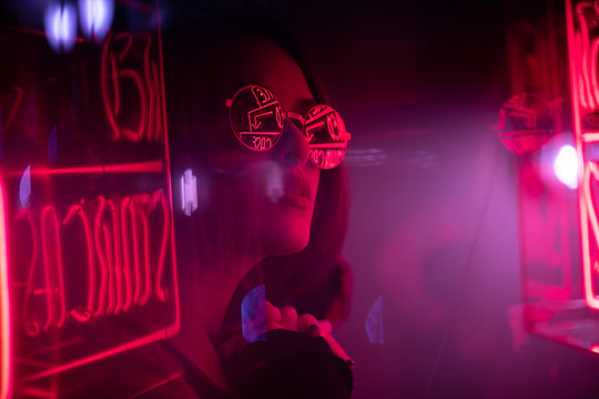 Long hair girl with sunglasses and leather jacket looking at neon lights
