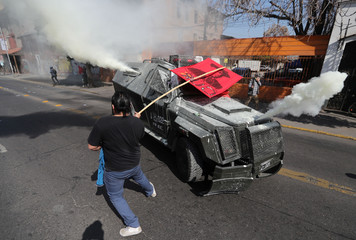 Demonstrators clash with riot police during a march and protest ahead of the anniversary of the country's 1973 military coup on September 11, in Santiago
