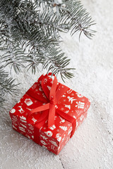 Christmas red gift box with festive pattern under snowy fir tree