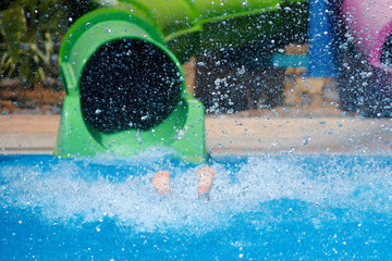 Colorful plastic water slides in waterpark. There are extensive splashes left by people having fun. Legs sticking out of the water.