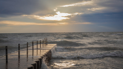 Concrete pier leading out to epic waves