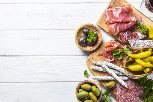 Italian antipasto with salami, jamon and olives on white.