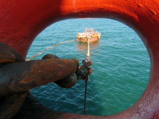 Offshore oil loading from single buoy mooring into oil tanker. Single buoy mooring serves as mooring point for tankers loading and offloading gas and liquids