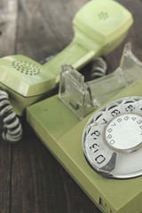 Green old-fashioned telephone on wooden background