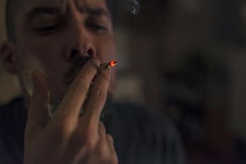 profile of a bearded man smoking a marijuana joint