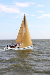 Sailboat yacht among the sea waves.