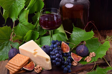 Red wine in a glass surrounded by the snacks: Maasdam cheese, figs, walnuts and a bunch of Isabella grapes on a wooden board