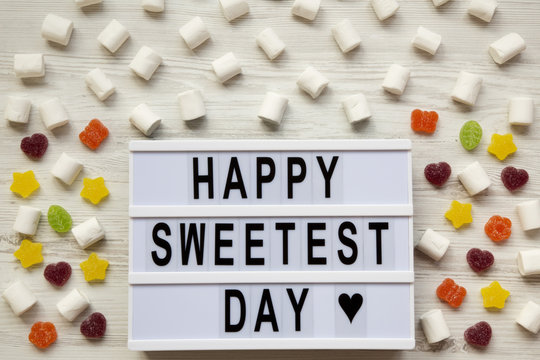 Modern board with text 'Happy Sweetest Day' word and candy over white wooden surface, top view. From above, flat lay, overhead.