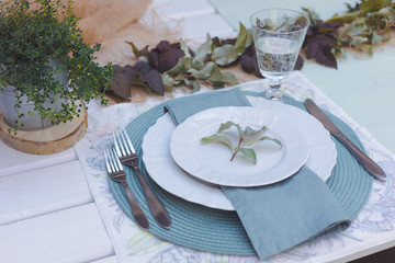 Holiday Summer or early autumn outside table setting with linen napkins and green leaves. Close up
