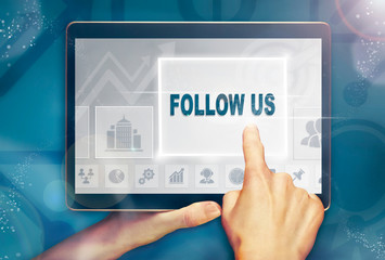 A hand selecting a Follow Us business concept on a clear screen with a colorful blurred background.