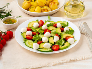 Fresh salad with tomatoes cucumbers arugula mozzarella and avocado. Oil with spices, baked potatoes, side view close up