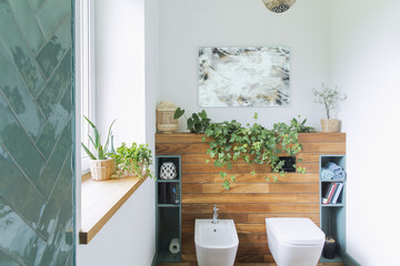 Cozy and mediterranean stylish bathroom in warm colours and natural wood. Wooden shelfs and white background.