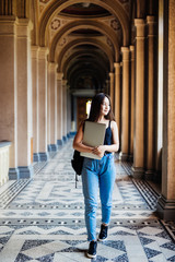 Young asian student girl holding laptop in hands while standing in University hall before classes.