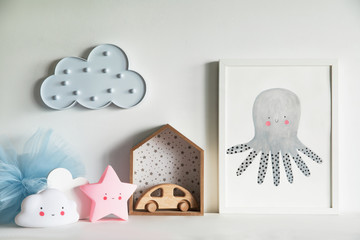 The modern scandinavian newborn baby room with mock up poster frame, wooden car, stars, toys and clouds. Minimalistic and cozy interior with white walls.